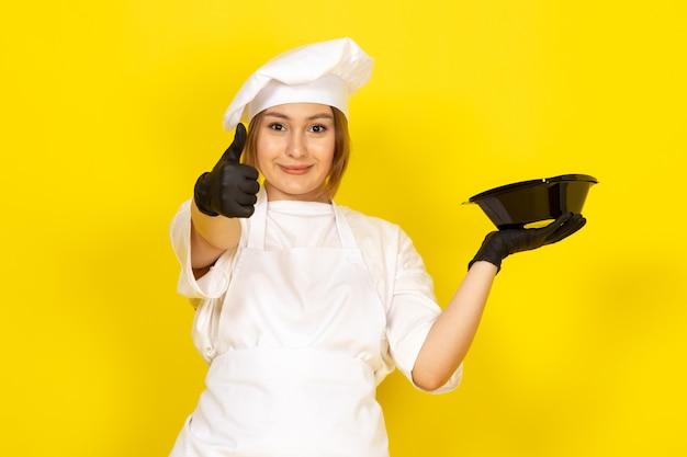Jonge vrouwelijke koken in witte cook pak en witte dop in zwarte handschoenen met zwarte kom