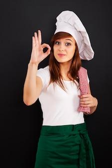 Jonge vrouwelijke kokende chef-kok die ok teken toont