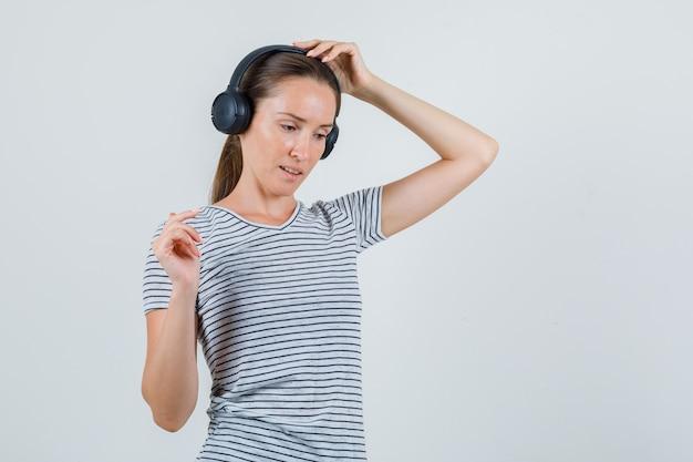 Jonge vrouwelijke koptelefoon in gestreept t-shirt aan te raken en peinzend op zoek. vooraanzicht.