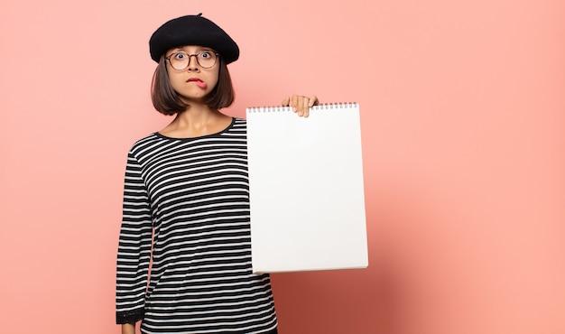 Jonge vrouwelijke kunstenaar die verbaasd en verward kijkt, lip bijtend met een nerveus gebaar, het antwoord op het probleem niet weet
