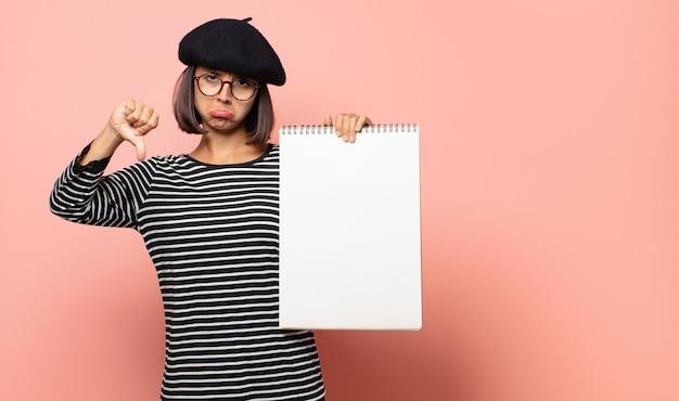 Jonge vrouwelijke kunstenaar die zich boos, boos, geïrriteerd, teleurgesteld of ontevreden voelt, duimen naar beneden toont met een serieuze blik