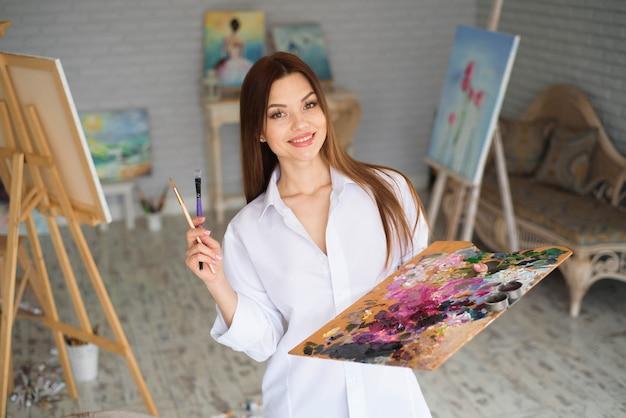 Jonge vrouwelijke kunstenaar schilderij foto in de studio