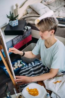 Jonge vrouwelijke kunstenaar schildert thuis in een creatieve studioomgeving studio