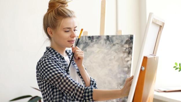 Jonge vrouwelijke kunstenaar tekent een schilderij op doek met een penseel en olie