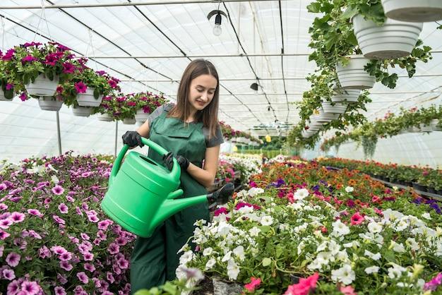 Jonge vrouwelijke kwekerij schoonheid bloemen in haar kas drenken