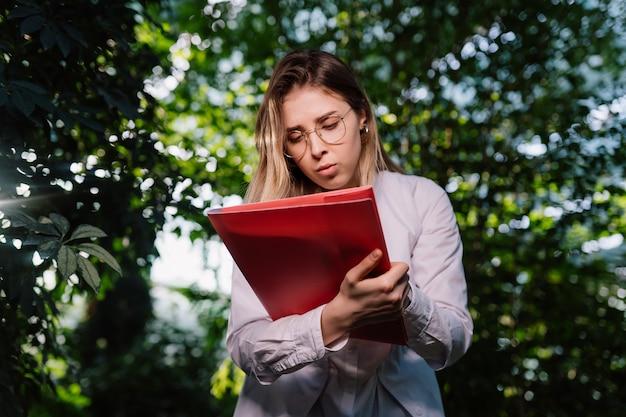 Jonge vrouwelijke landbouwingenieur die in serre werkt