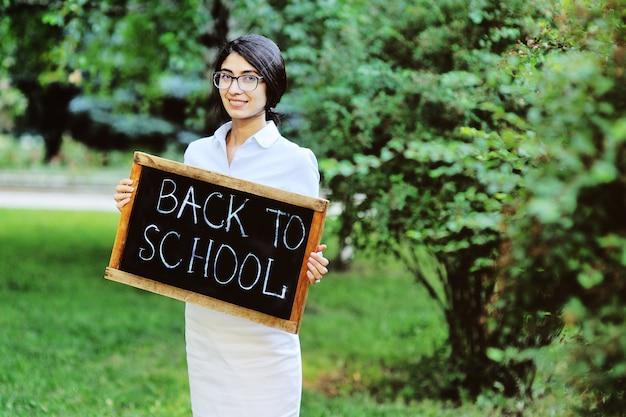 Jonge vrouwelijke leraar die in elegante kleren en glazen een teken houdt