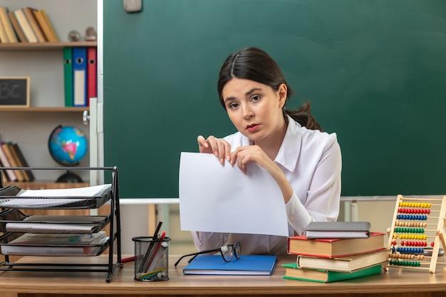Jonge vrouwelijke leraar die papier vasthoudt aan tafel met schoolhulpmiddelen in de klas
