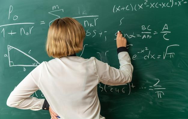 Jonge vrouwelijke leraar die voor het bord staat en iets op het bord schrijft met gestrand voor bord in de klas
