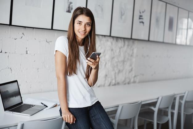 Jonge vrouwelijke leraar luisteren naar online streaming muziek buiten de klas met behulp van een smartphone en een laptop ter voorbereiding op haar lezingen.