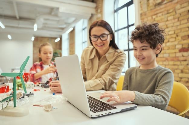 Jonge vrouwelijke leraar met een bril die laptop gebruikt in de klas met wetenschappelijke robotica-video om