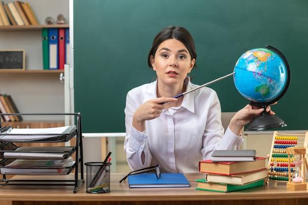 Jonge vrouwelijke leraar zittend aan tafel met schoolhulpmiddelen die de aanwijzer vasthouden en op de wereldbol in de klas zetten