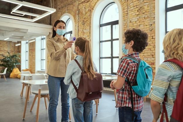 Jonge vrouwelijke lerares die een beschermend masker draagt, screent schoolkinderen op koorts tegen de verspreiding