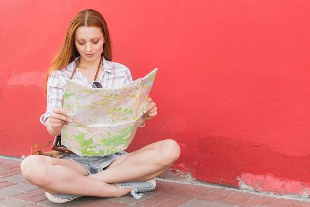 Jonge vrouwelijke lezing kaart zittend op de grond