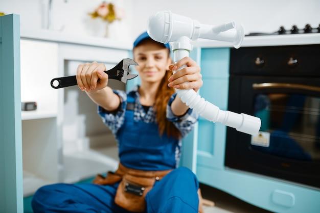 Jonge vrouwelijke loodgieter in uniform toont moersleutel en pijp in de keuken. klusjesvrouw met gereedschapstas reparatie gootsteen, sanitair service aan huis