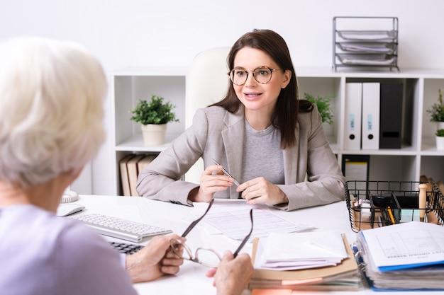 Jonge vrouwelijke maatschappelijk werker in jasje aan tafel zitten en praten met senior dame tijdens het geven van haar raadpleging