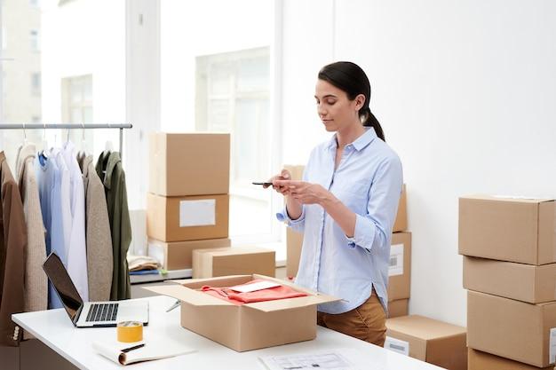 Jonge vrouwelijke manager die met mobiele telefoon ingepakte kleren in open doos fotografeert alvorens de opdracht naar cliënt te verzenden