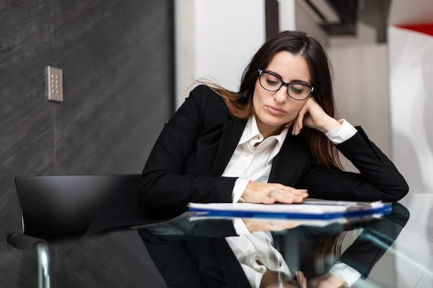 Jonge vrouwelijke manager zit een ther bureau in een modern kantoor en kijkt verveeld