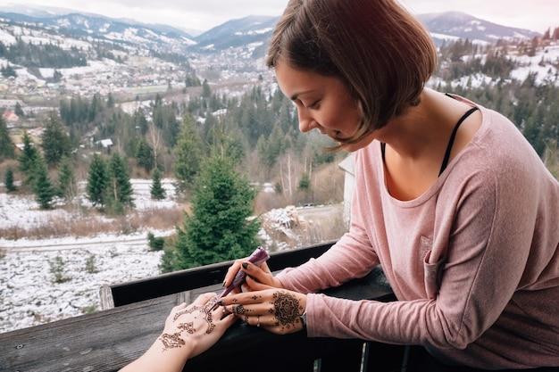 Jonge vrouwelijke mehndi kunstenaar in karpaten dorp