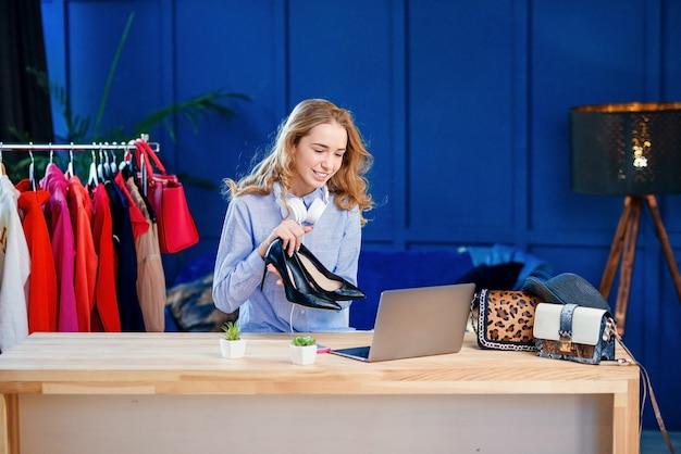 Jonge vrouwelijke mode blogger die paar schoenen presenteert