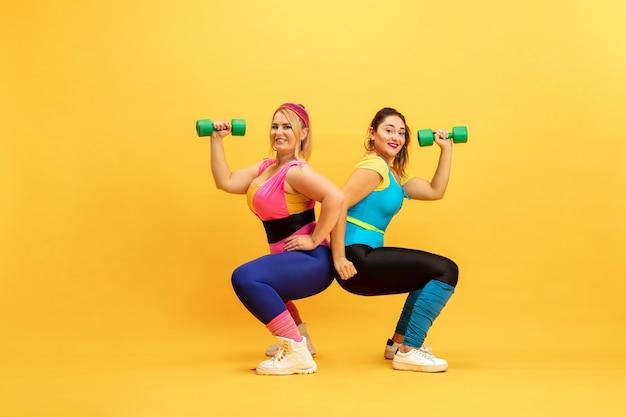 Jonge vrouwelijke modellen trainen op gele muur