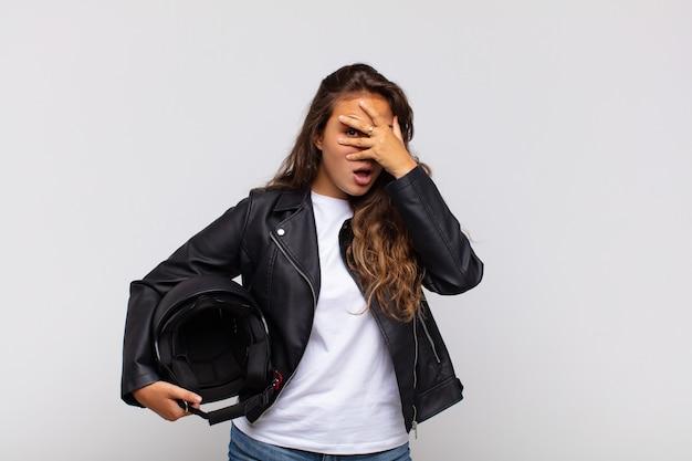 Jonge vrouwelijke motorrijder die geschokt, bang of doodsbang kijkt, het gezicht bedekt met de hand en tussen de vingers gluurt