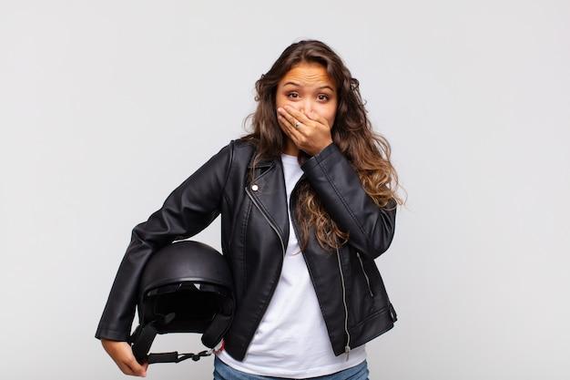 Jonge vrouwelijke motorrijder die mond bedekt met handen met een geschokte, verbaasde uitdrukking, een geheim houdt of oeps zegt