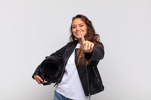 Jonge vrouwelijke motorrijder die trots en zelfverzekerd glimlacht en nummer één triomfantelijk poseert en zich een leider voelt