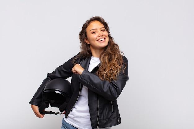 Jonge vrouwelijke motorrijder die zich gelukkig, positief en succesvol voelt, gemotiveerd wanneer ze voor een uitdaging staan of goede resultaten vieren