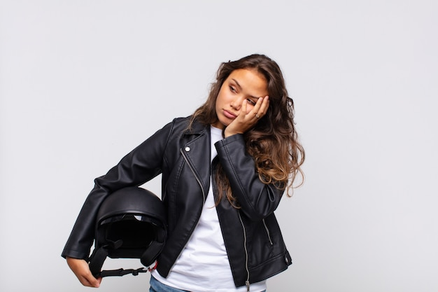 Jonge vrouwelijke motorrijder die zich verveelt