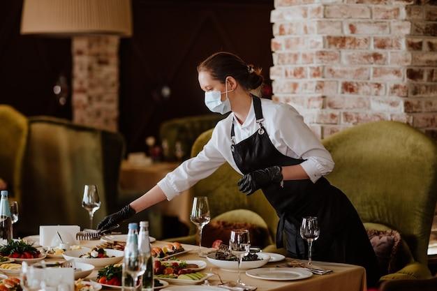 Jonge vrouwelijke ober in uniform met medische masker en handschoenen die in het restaurant dienen. kopieer ruimte.