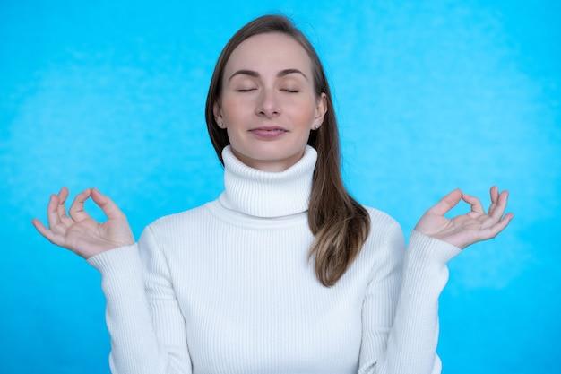 Jonge vrouwelijke ogen gesloten houden tijdens het beoefenen van yoga binnenshuis, mediteren, hand in hand in mudra gebaar