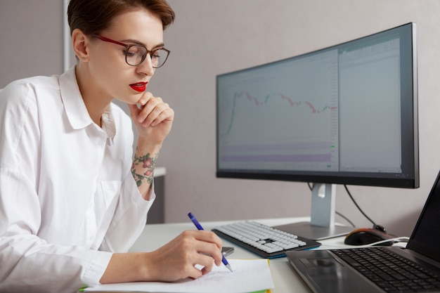 Jonge vrouwelijke ondernemer die aan haar computer werkt