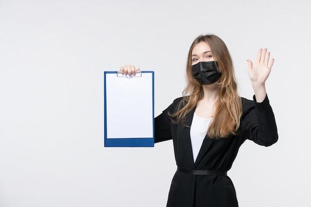 Jonge vrouwelijke ondernemer in pak die haar medisch masker draagt en documenten opheft met vijf op een witte muur