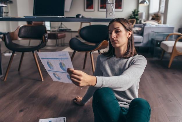Jonge vrouwelijke ondernemer leest documenten, bestudeert informatie, analyseert gegevens.