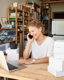 Jonge vrouwelijke ondernemersontwerper die op mobiele telefoon spreekt