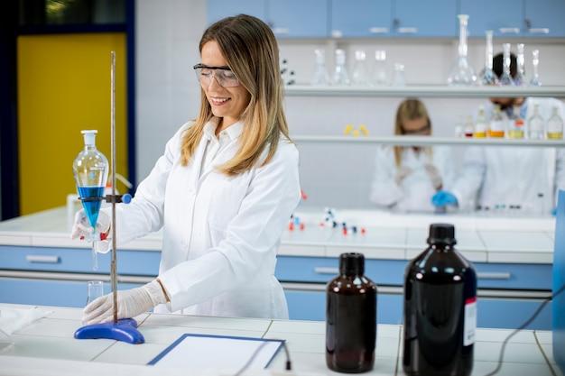 Jonge vrouwelijke onderzoeker die met blauwe vloeistof bij scheitrechter in het laboratorium werkt