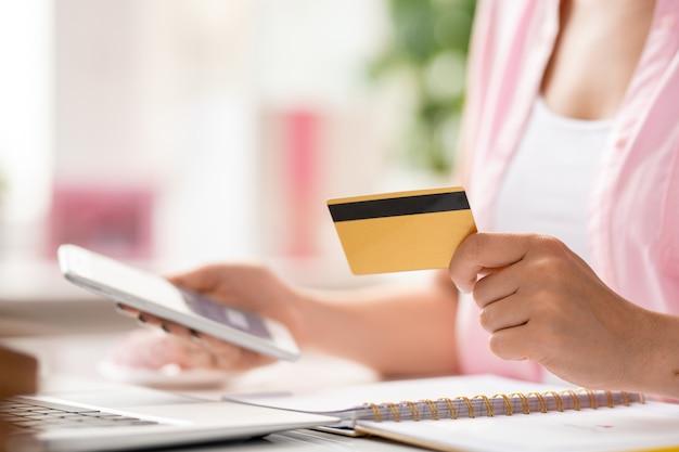 Jonge vrouwelijke online shopper met smartphone met behulp van plastic kaart om te betalen voor bestelling tijdens het invoeren van gegevens