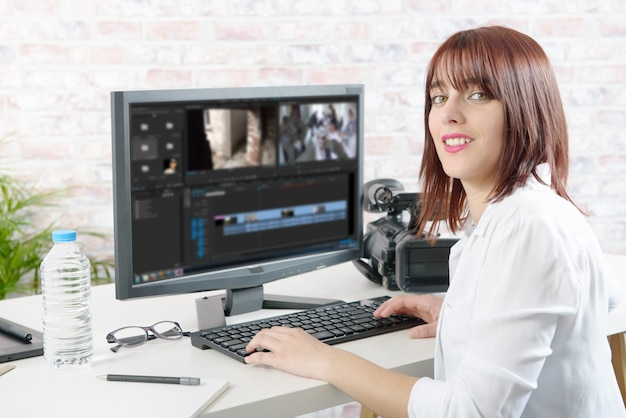 Jonge vrouwelijke ontwerper die computer voor videobewerking met behulp van