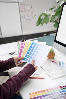 Jonge vrouwelijke ontwerper die de juiste kleuren voor een logo kiest