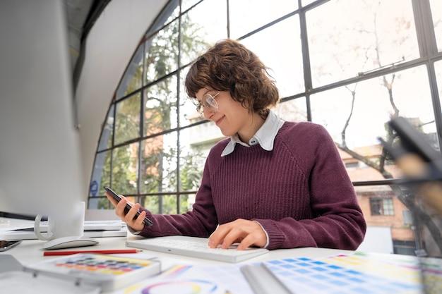 Jonge vrouwelijke ontwerper die haar smartphone controleert
