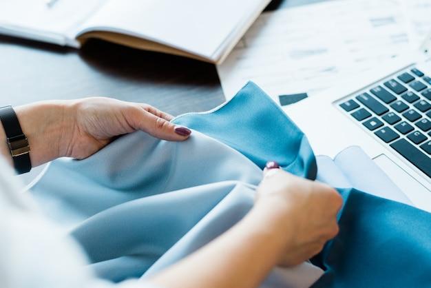 Jonge vrouwelijke ontwerper die twee textielmonsters vergelijkt terwijl ze een geschiktere kiest voor een nieuwe modecollectie