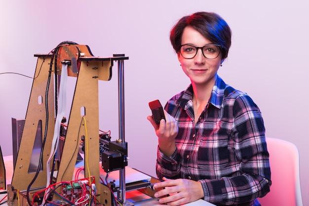 Jonge vrouwelijke ontwerperingenieur die een printer in het laboratorium gebruikt en een productprototype, technologie en innovatieconcept bestudeert.