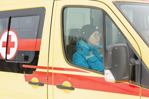 Jonge vrouwelijke paramedicus in uniform en pet zit in ambulanceauto terwijl hij zich haast om zieke te helpen en te redden
