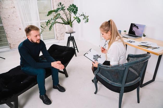 Jonge vrouwelijke patiënt die inkblot van rorschach met psycholoog in bureau bekijkt