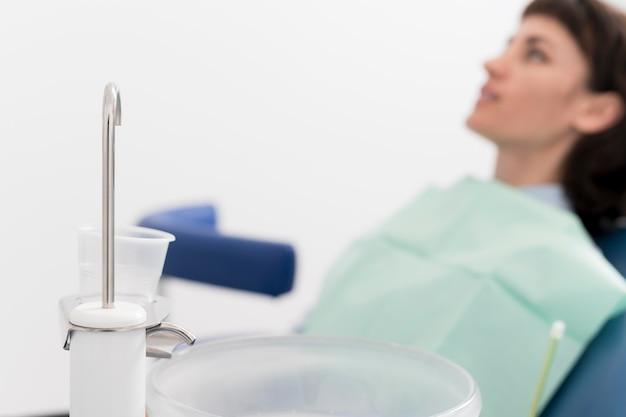 Jonge vrouwelijke patiënt die wacht op een tandheelkundige ingreep bij de tandarts