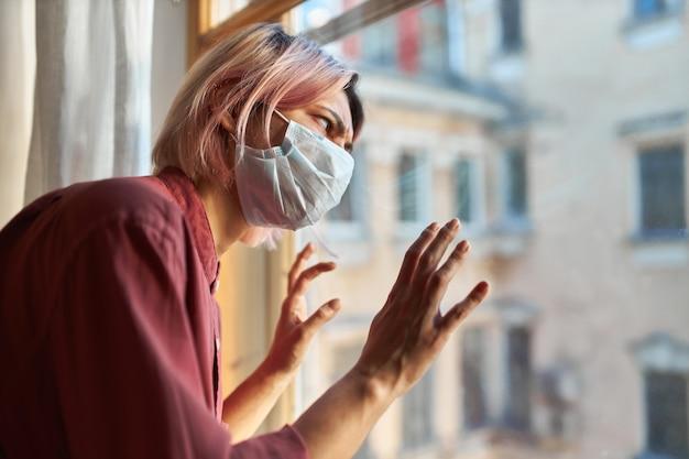 Jonge vrouwelijke patiënt met covid-19-symptomen moet tijdens quarantaine in het ziekenhuis blijven, bij het raam staan in een wegwerpbaar chirurgisch masker, met een gespannen paranoïde blik, de handen op het glas houden