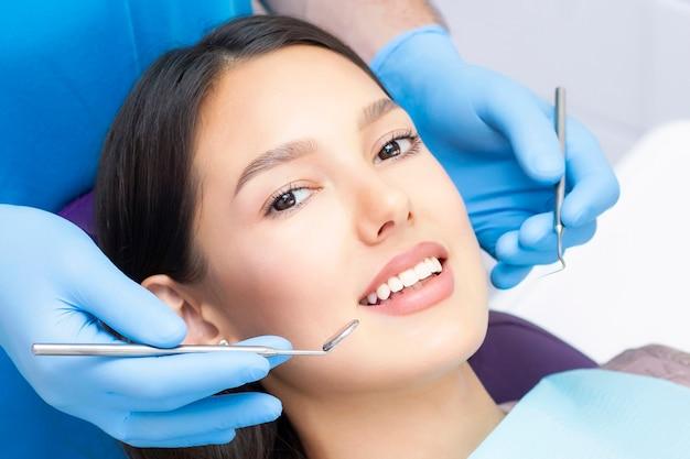 Jonge vrouwelijke patiënt met mooie glimlach die tandheelkundige inspectie onderzoekt in de tandartskliniek. gezonde tanden en medicijnen, stomatologieconcept