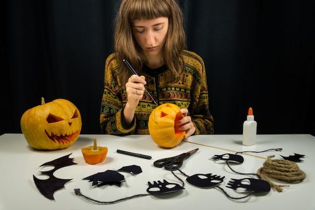 Jonge vrouwelijke persoon die jack'o'lantern snijdt voor halloween