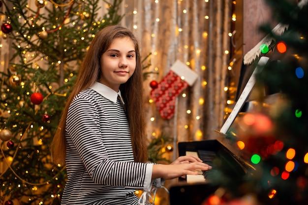 Jonge vrouwelijke pianist met lang haar in een jurk die bij de piano zit en in de camera kijkt. kerstversiering rondom in de kamer, feestelijke stemming.